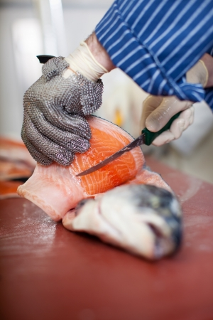 Closeup of male workers hands cutting fish with knife at table