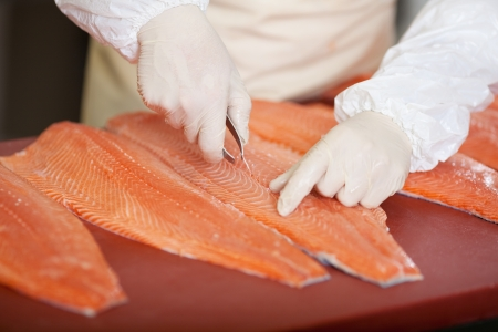 worker´s hand deboning salmon at fish market photo