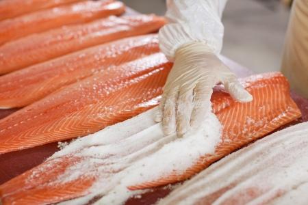 テーブルの上スライスされた魚に塩を適用する労働者の手のクローズ アップ 写真素材