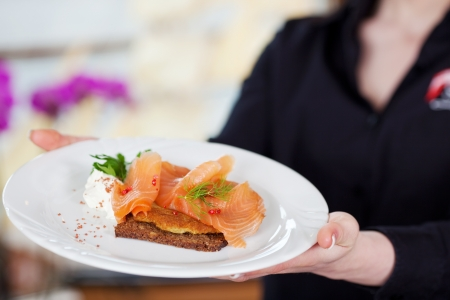 salmon dinner: midsection view of a waitress serving salmon on bread