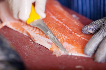 close-up of worker cutting salmon fillets with a knife photo