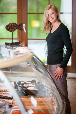 fish store: Retrato de mujer joven feliz de pie junto vitrina en la tienda de peces