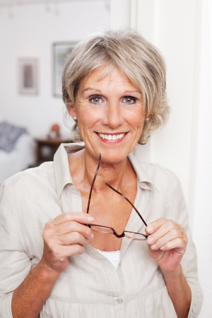 the elderly residence: Modern older woman standing in her house holding her glasses in her hand smiling at the camera