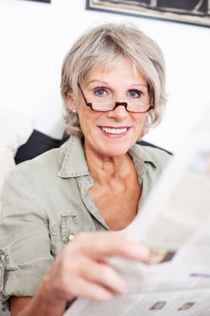 Retired woman wearing glasses sitting reading a newspaper at home on a sofa photo