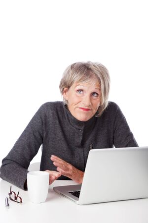 Senior woman having trouble with her computer shrugging her shoulders and looking to heaven for inspiration as she sits in front of her laptop Stock Photo - 21213358