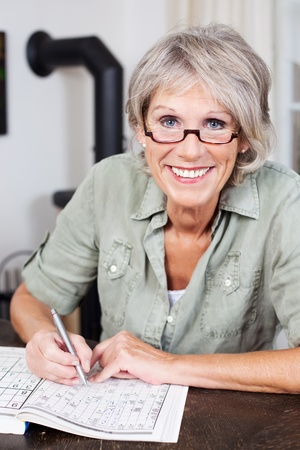 Smiling attractive elderly woman wearing glasses sitting at a table doing a crossword puzzle in a book photo