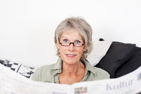 Senior lady reading her newspaper at home relaxing on a couch and peering over the top at the viewer photo
