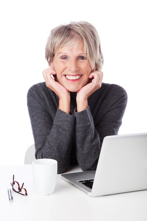 beautiful middle aged woman: Modern retired woman with a laptop computer leaning her chin on her hands smiling at the camera