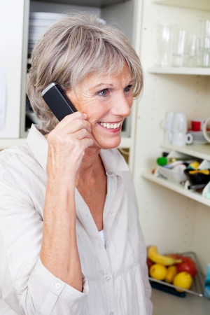 phone handset: Trendy older woman with a lively smile standing in her kitchen talking on the phone Stock Photo
