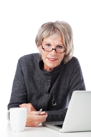 Old woman working with her laptop with a cup of coffee on her side photo