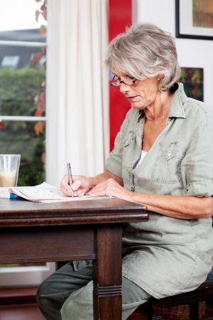 Portrait of a senior woman sitting at a wooden table in her living room at home writing notes in a notebook photo