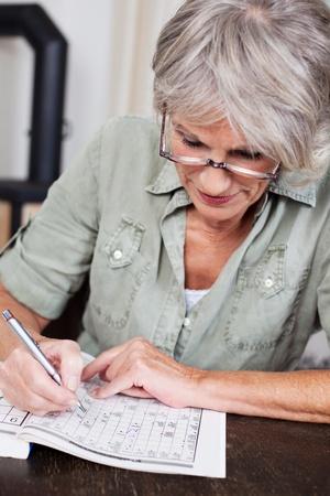 personen: Senior vrouw zittend aan een tafel draagt een leesbril te concentreren op het invullen van een kruiswoordpuzzel