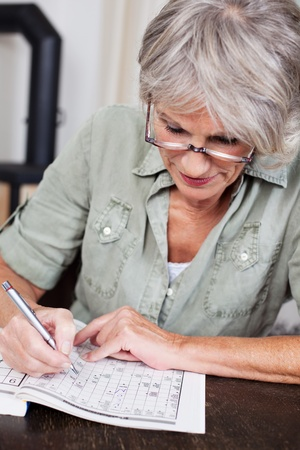 Senior woman sitting at a table wearing reading glasses concentrating on completing a crossword puzzle Imagens