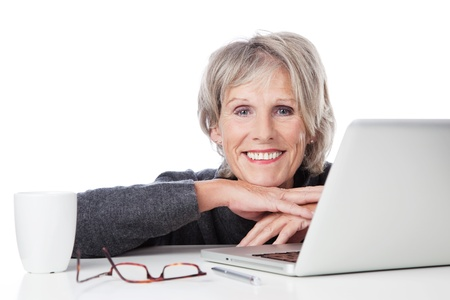 Smiling old woman resting on the table with laptop and cup of coffee photo