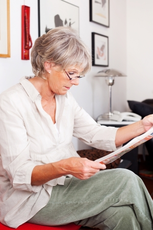 Trendy modern senior woman wearing glasses sitting in her living room reading a newspaper, sideways portrait photo