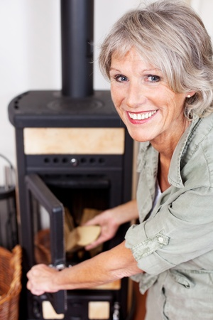 wood stove: Senior woman putting logs into the woodburner stove at home to heat the house during winter looking back at the camera with a smile Stock Photo