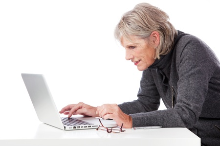 concentrates: Senior woman concentrating and bending forwards to peer at the screen when using her laptop