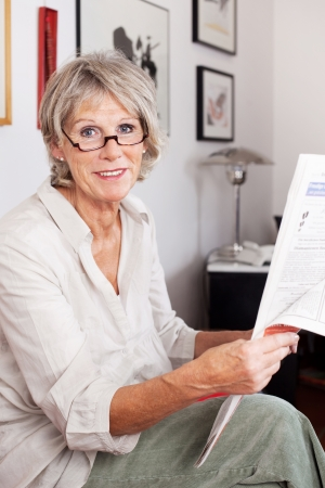 wearing glasses: Elderly grey haired attractive woman wearing reading glasses sitting in her living room enjoying reading the newspaper