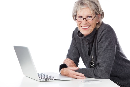 savvy: Smiling senior woman sitting at a white table in her glasses using a laptop computer on white