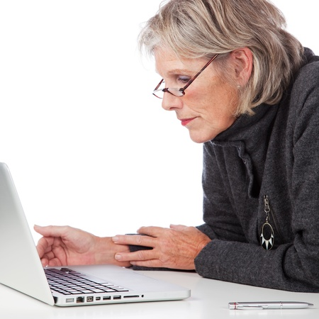 Profile portrait of an attractive senior woman working on a laptop leaning forwards to peer at something on the screen photo