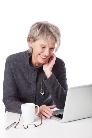 Senior woman surfing the internet and smiling in amusement at the information on the screen of her laptop computer photo