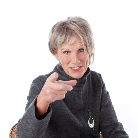 vivacious: Attractive grey haired senior woman sitting in a chair pointing at the viewer identifying a particular person, making a choice or showing a direction Stock Photo