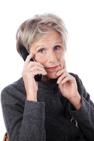grey haired: Concerned attractive grey haired senior woman with a worried expression using a wireless telephone isolated on white