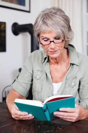 concentrating: Senior woman sitting at a table reading a book with reading glasses is totally immersed in the story