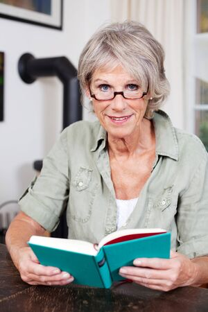 woman wearing glasses: Attractive elderly woman wearing glasses sitting at a table in her home reading a book and looking up to smile at the camera Stock Photo