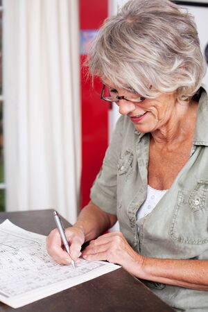 crossword puzzle: Elderly woman sitting at a wooden table in her living room solving a crossword puzzle