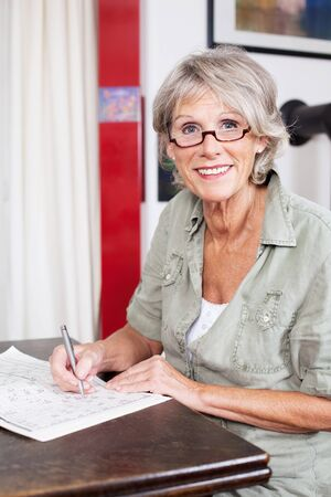 clues: Attractive senior woman wearing glasses completing a crossword puzzle sitting at a small wooden table in her house Stock Photo