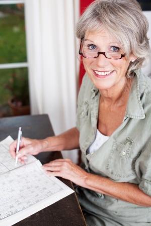 1 senior: Mujer mayor con gafas de trabajo en un crucigrama en un sittiing libro de rompecabezas en una peque�a mesa de madera en su casa