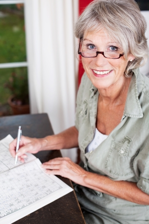 Older woman wearing glasses working on a crossword puzzle in a puzzle book sittiing at a small wooden table in her house Stock Photo