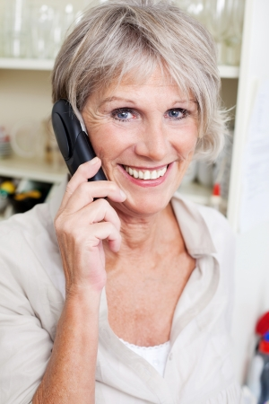 Smiling attractive grey haired senior lady talking on a telephone in her house photo