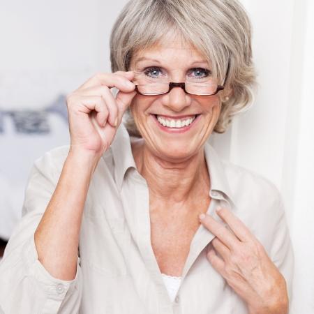 jubilados: Feliz atractiva dama de alto nivel con una hermosa sonrisa llevaba gafas de lectura y mirando por encima de la parte superior en el espectador