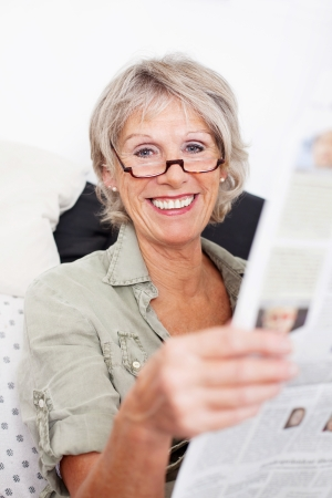 big smile: Happy grey haired senior retired woman wearing spectacles sitting reading the newspaper with a big smile of appreciation on her face