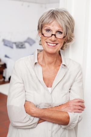 Lachende aantrekkelijke senior vrouw draagt een bril met gevouwen armen