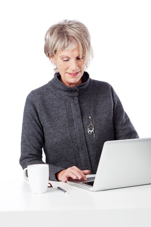 Senior attractive female office worker seated at a white desk using a laptop computer against a white background photo