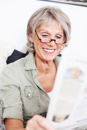 grey haired: Elderly grey haired lady wearing a pair of reading glasses sitting reading the newspaper with a smile