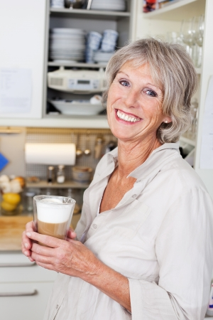 attracive: Attracive modern elderly woman enjoying a cup of cappuccino in her kitchen smiling in appreciation Stock Photo