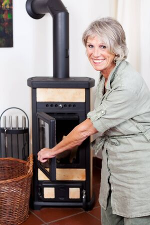 Attractive smiling senior lady puting wood in the stove or woodburner to heat her house during winter photo