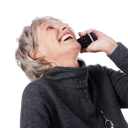 Low angle portrait of an attractive vivacious senior lady on the telephone laughing while enjoying the conversation, isolated on white photo