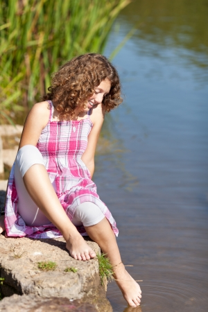 Happy Teenage girl dipping foot in water photo