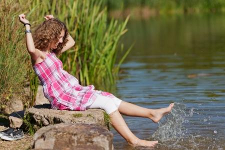 manos y pies: Vista lateral del adolescente con los brazos levantados sentado en la roca, mientras que las salpicaduras de agua en el lago