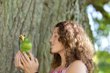 puckering lips: Closeup of teenage girl kissing toy frog against tree trunk in park Stock Photo