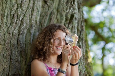 lupe: Happy young girl looking at leaf through magnifying glass against tree trunk in park Stock Photo