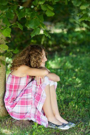 hugging knees: Thoughtful teenage girl looking away while sitting in park