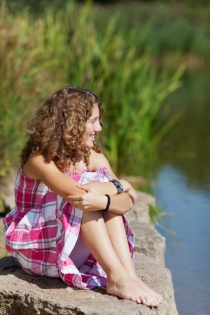 Thoughtful young girl sitting on rock while looking away by lake