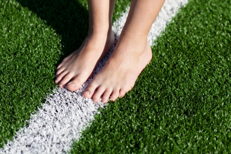 barefoot people: Low section of girl standing on white marking on sports field Stock Photo