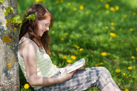 Side view of young girl leaning on tree trunk while reading book in park photo